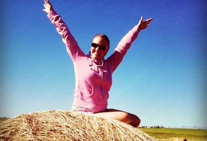 Shannon Fisher on a hay bale looking happy