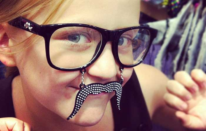 Emma with dark rim glasses and fake mustache