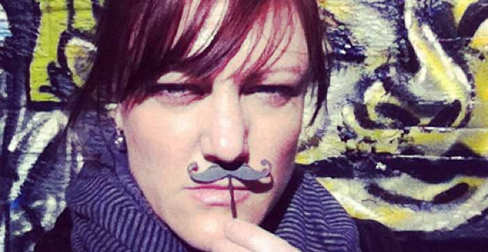 Shannon Fisher holding up a fake movember moustache