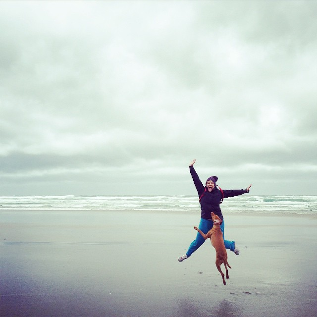 woman and dog jumping on a beach in the rain and wind